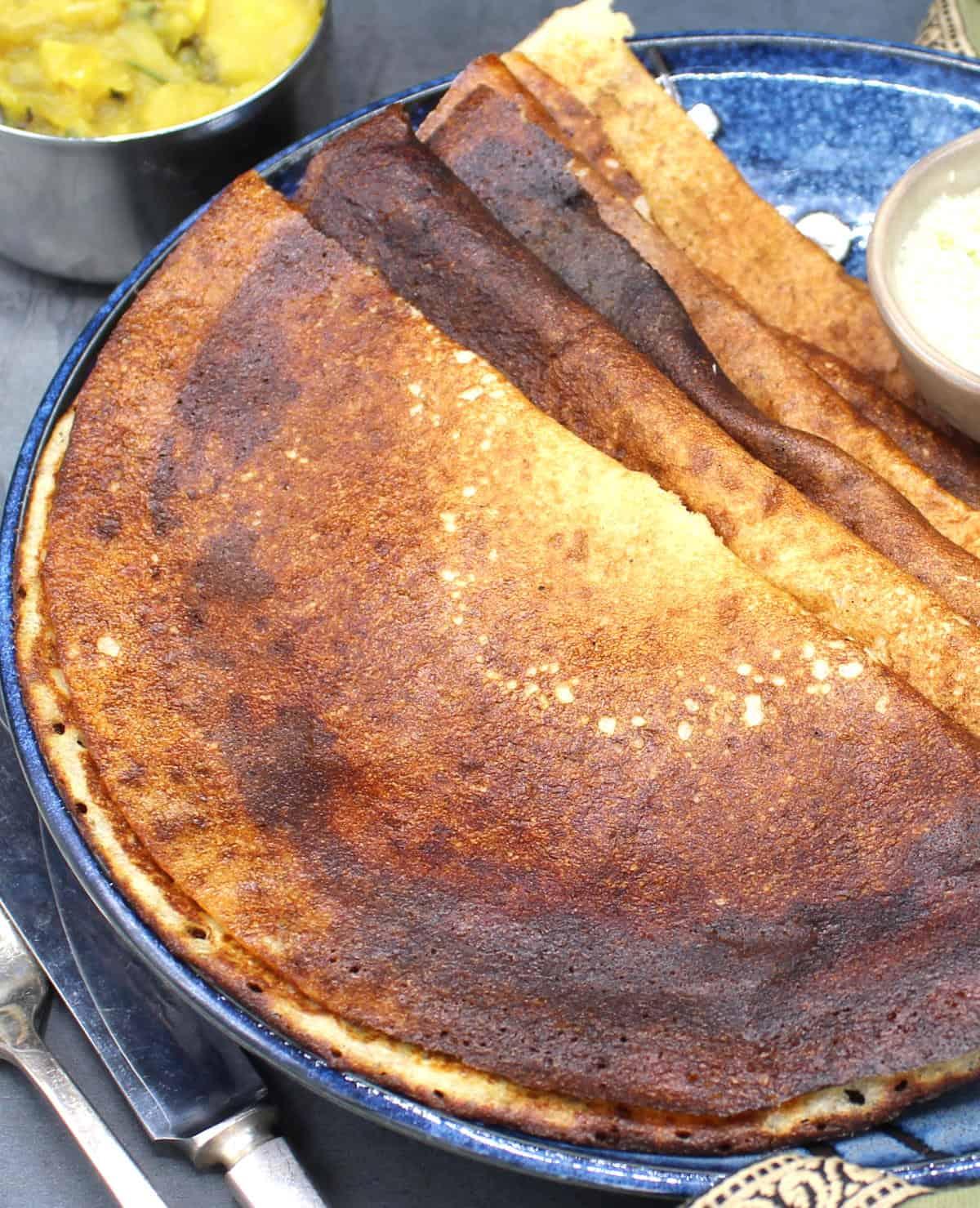 Front partial photo of quinoa dosa on plate with potato sabzi.