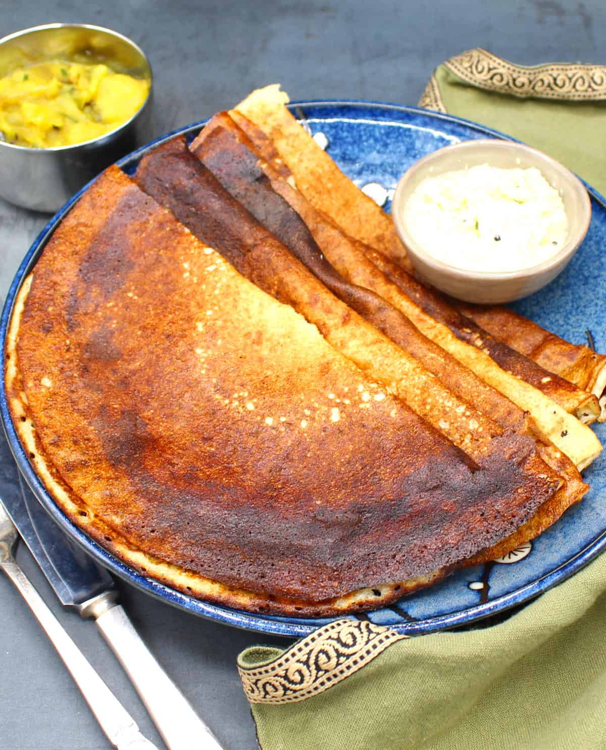 Blue plate with five quinoa dosas and a bowl of coconut chutney, fork and knife.