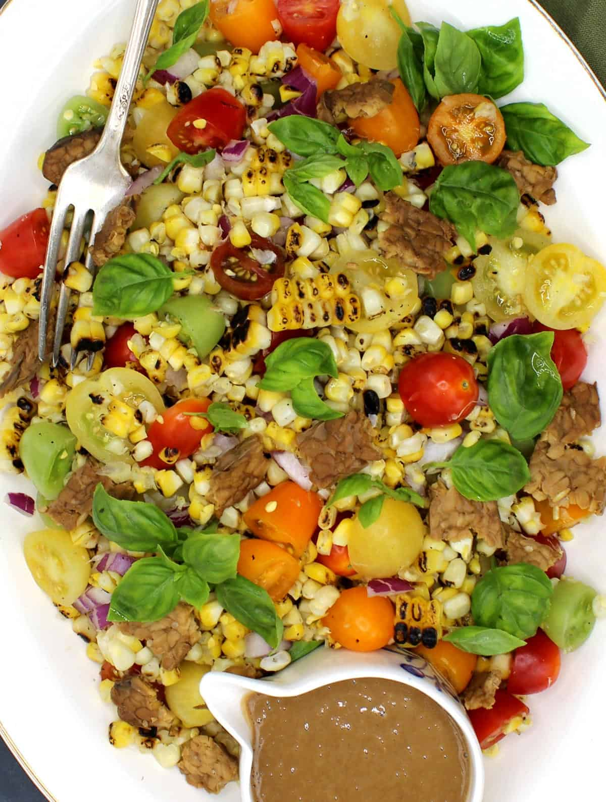 Tight closeup of a colorful grilled corn salad with tempeh bacon, cherry tomatoes, basil and creamy sesame dressing.