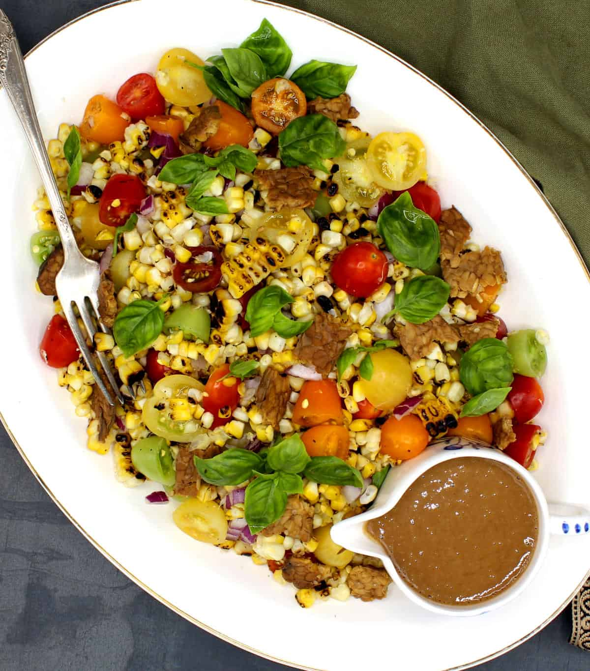 Overhead photo of grilled corn salad on a white platter with creamy sesame dressing on the side and a fork.