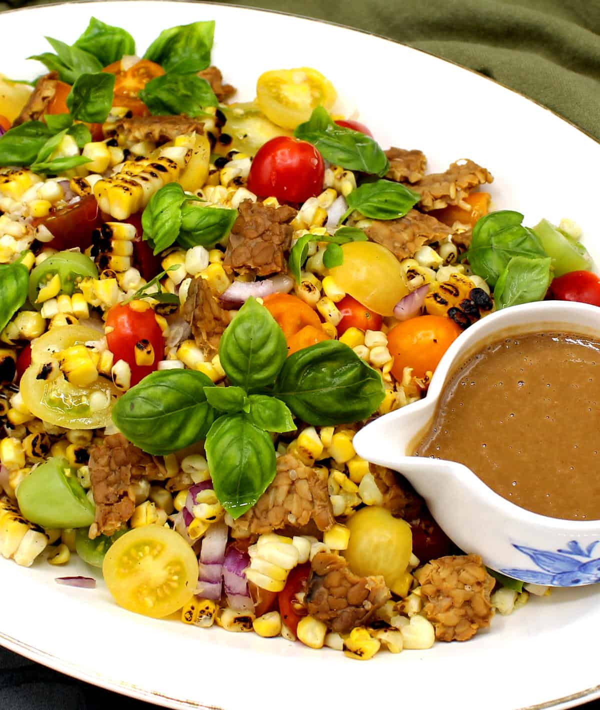 Closeup photo of grilled corn salad with cherry tomatoes, basil and creamy sesame dressing on a white platter.