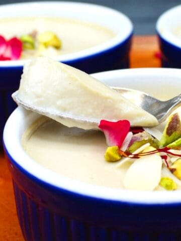 A scoop of vegan mishti doi from a blue and white ramekin with nuts, saffron and rose petals.