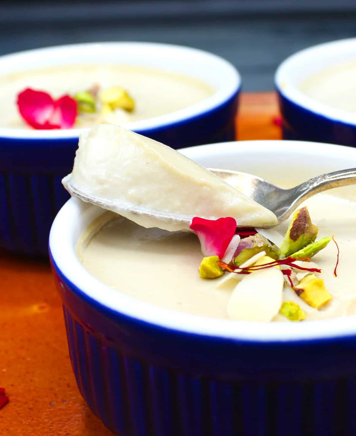 A spoon scooping up a bit of vegan mishti doi from a blue and white ramekin garnished with rose petals, pistachio, almonds and saffron.