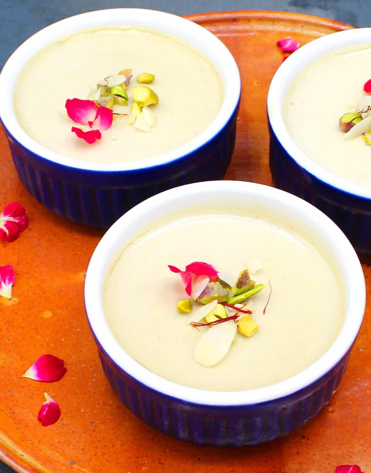 Front photo of ramekins of vegan mishti doi decorated with rose petals, saffron and nuts.