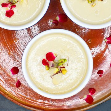 Ramekins with vegan mishti doi, rose petals, nuts and saffron
