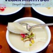 "Vegan mishti doi scooped with a spoon from blue and white ramekin with text inlay that says ""dairy-free, delicious vegan mishti doi, bengali sweetened yogurt"""