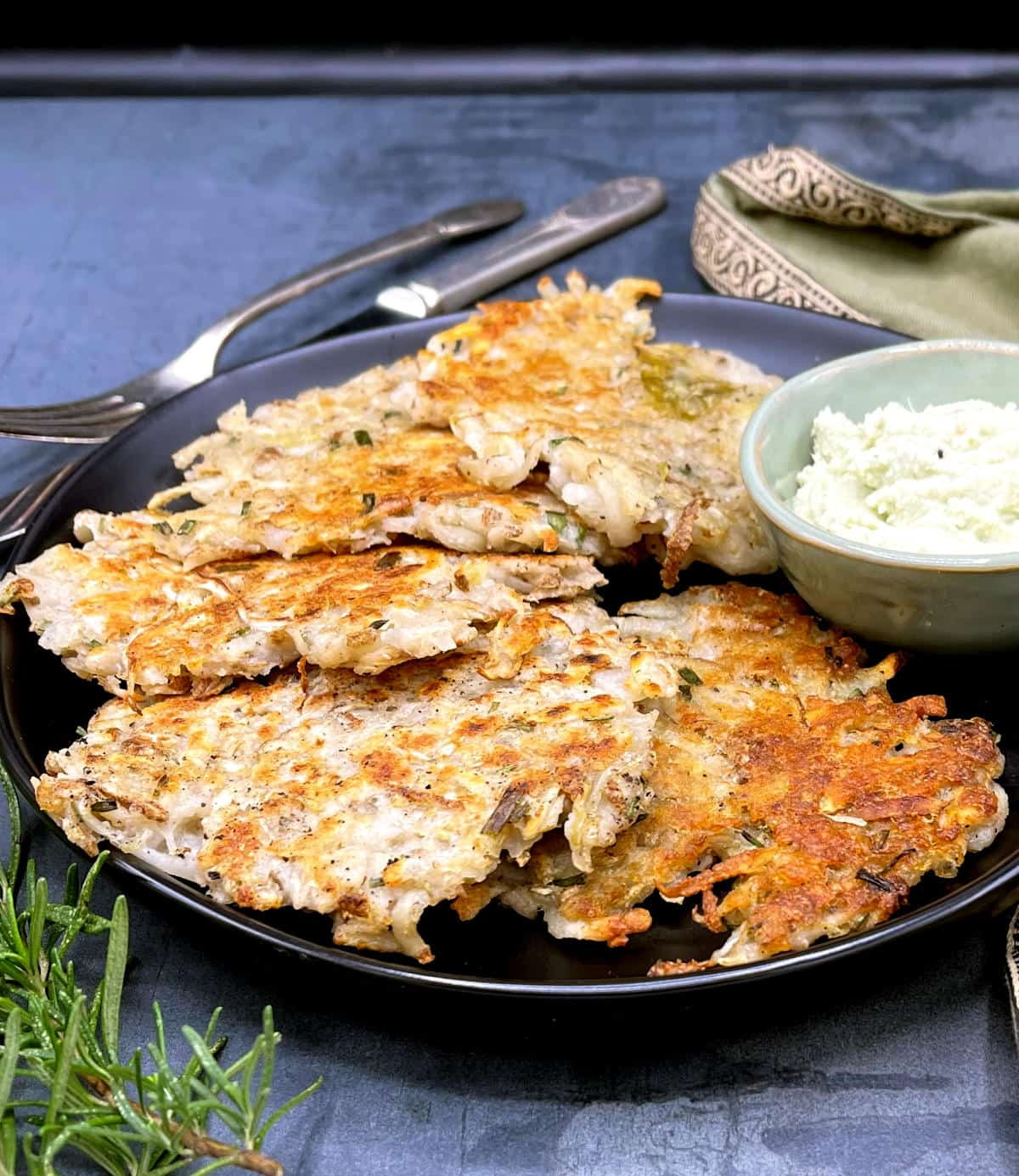 Potato Sauerkraut latkes in black plate with chutney, rosemary sprig and knife and fork.
