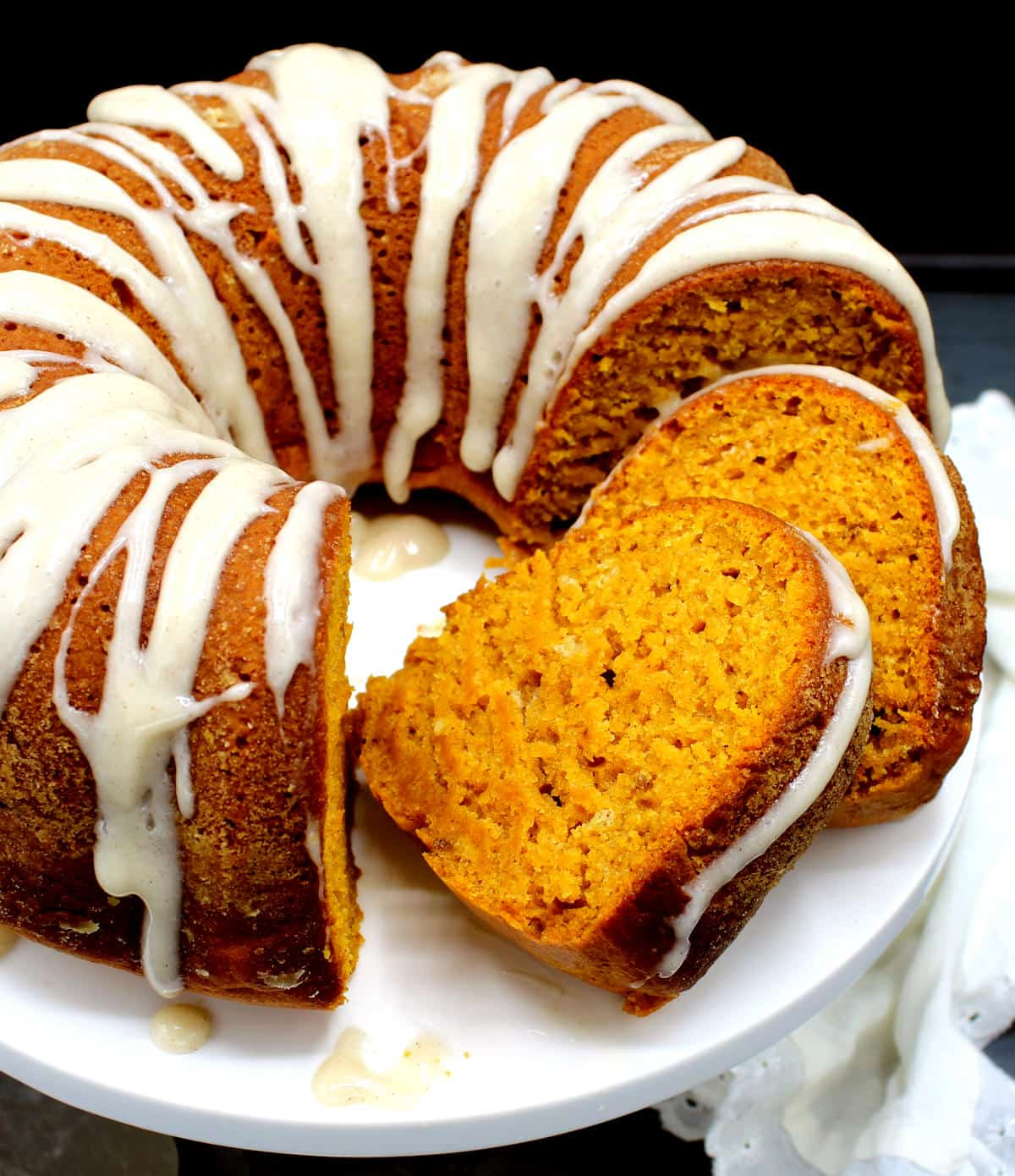 Closeup photo of pumpkin cake with vegan cream cheese glaze and two slices on cake stand.