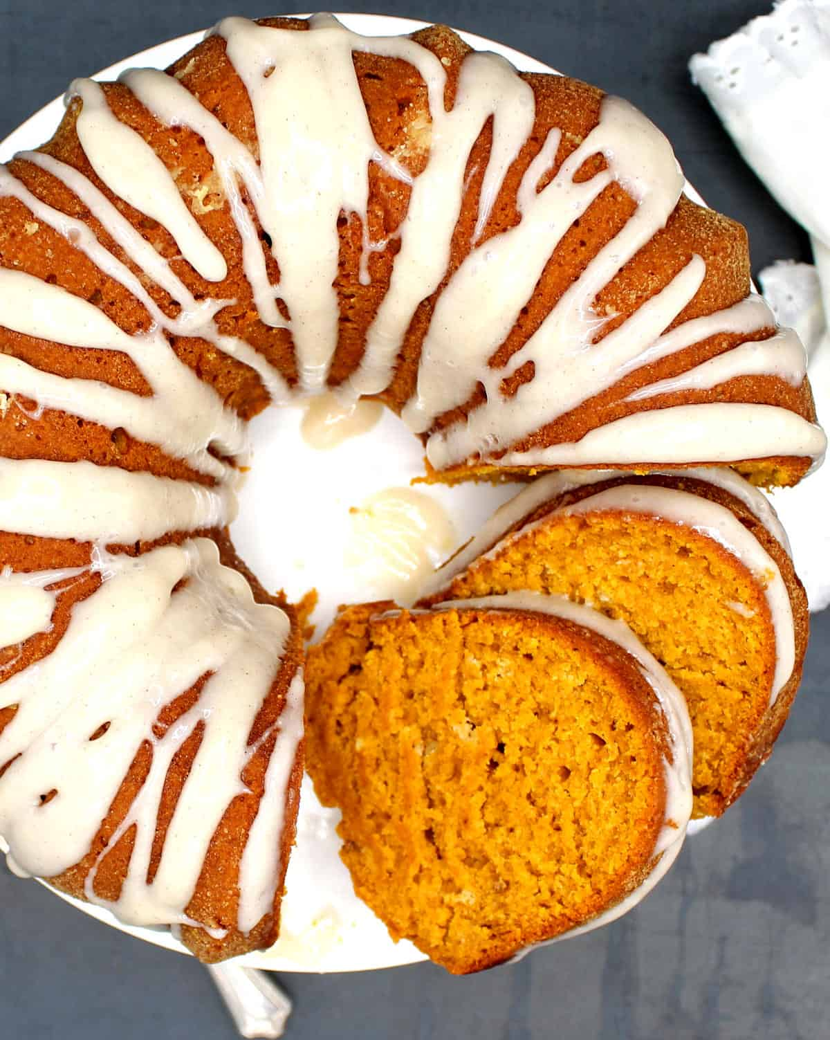 Overhead shot of a vegan chai spice pumpkin cake with two slices showing the tender, moist crumb.