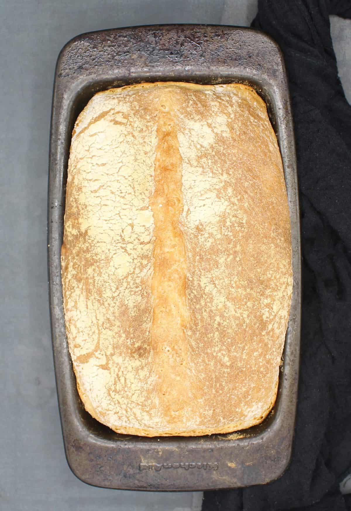Overhead photo of crusty homemade bread in bread pan.