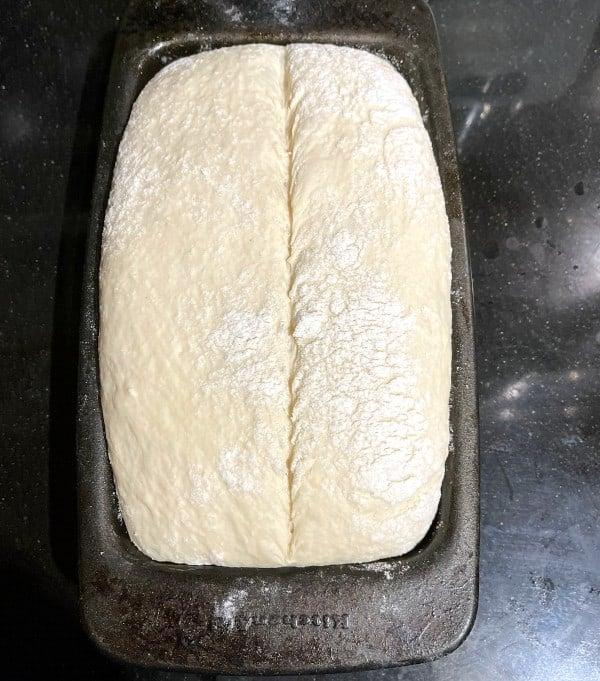 Scored bread dough in loaf pan