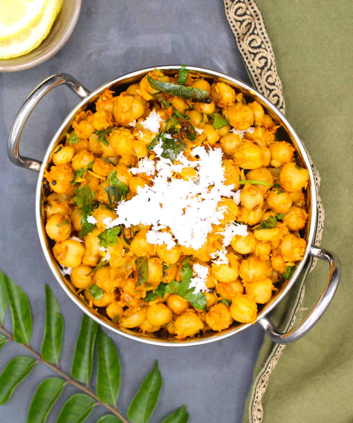 Overhead photo of a kadhai with chana sundal with curry leaves and lemon slices on the side.