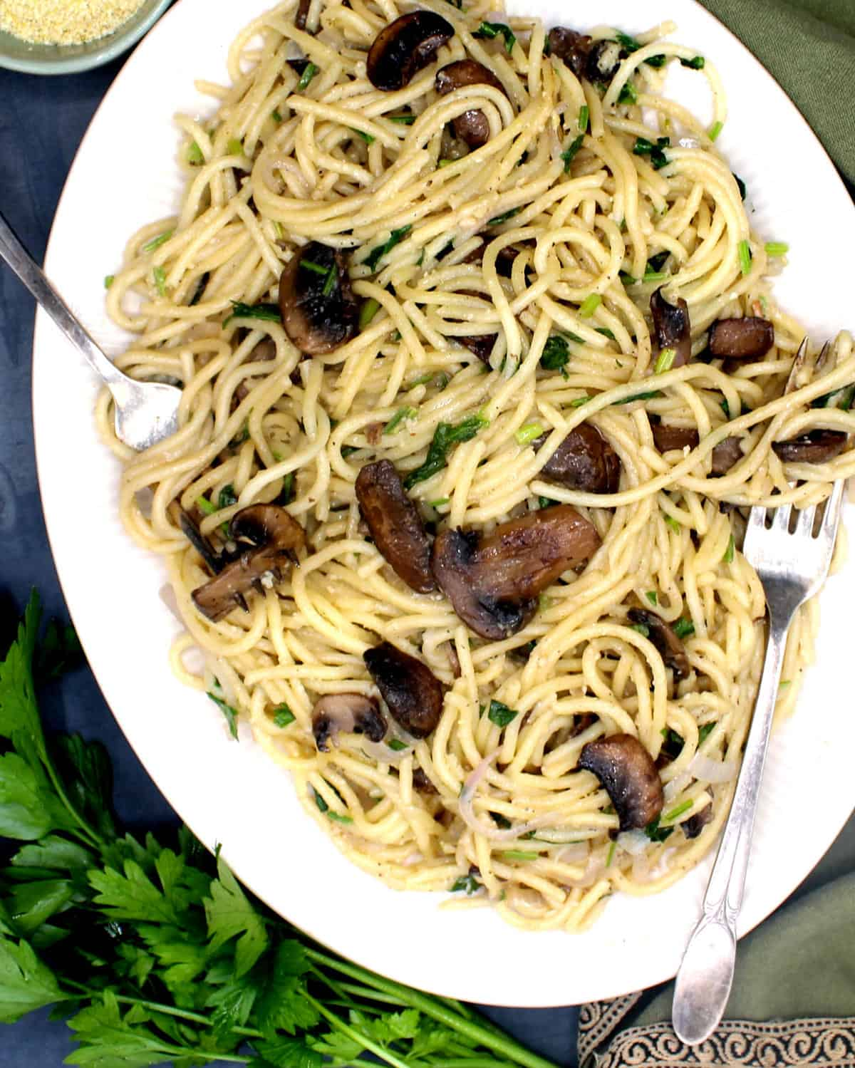 Overhead closeup shot of a large white platter filled with vegan pasta with mushrooms. Also pictured are forks and a bunch of parsley.