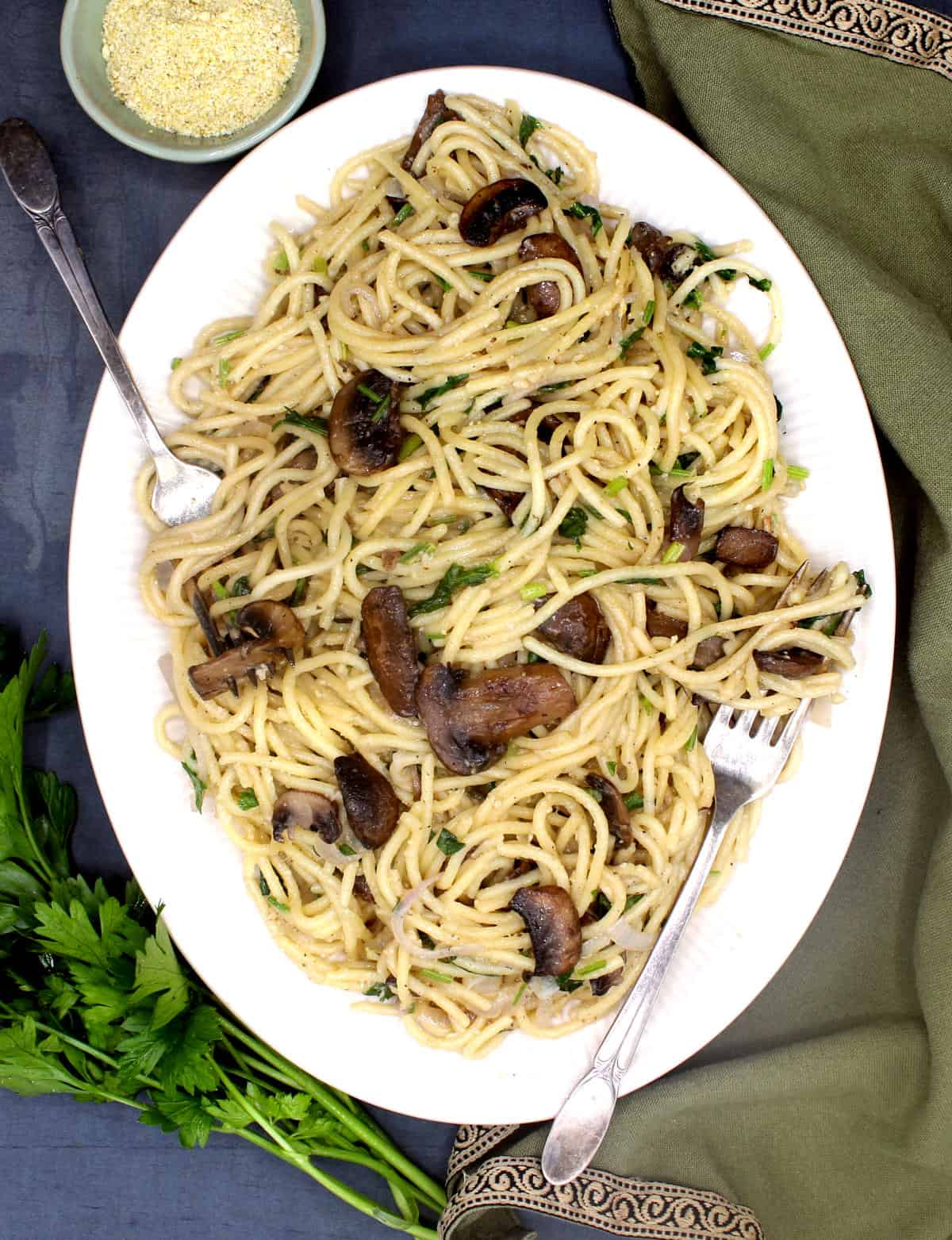 Overhead photo of vegan mushroom pasta with vegan parmesan and parsley and a green napkin on the side.