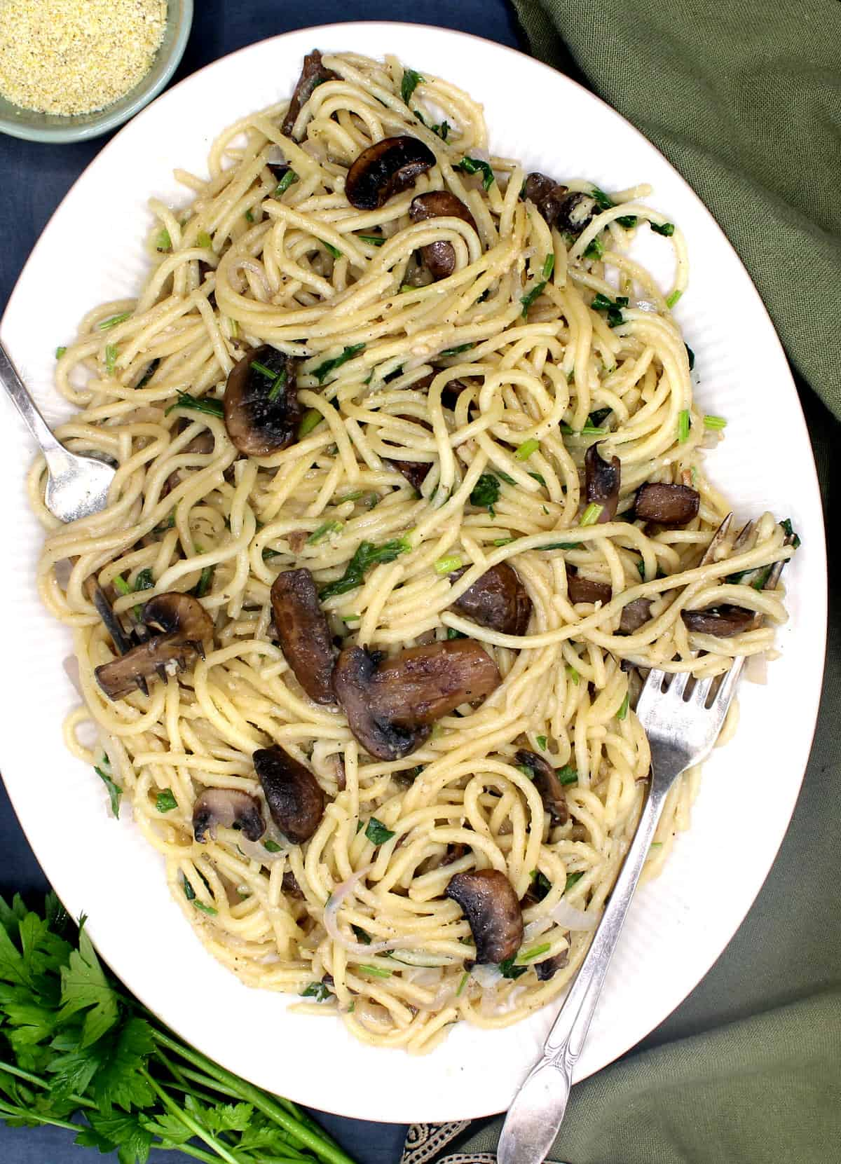 Overhead shot of a white, oval platter of spaghetti with crimini mushrooms, parsley and shallots. Two forks, a bunch of parsley and a green napkin are also in the picture.