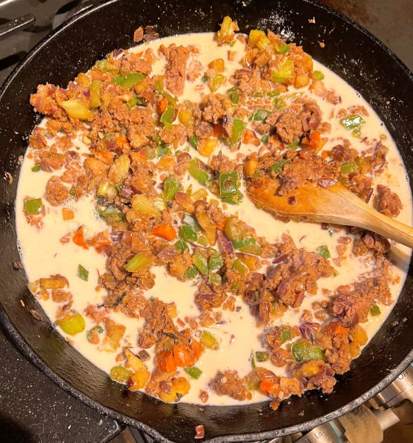 Oat milk added to skillet with veggies