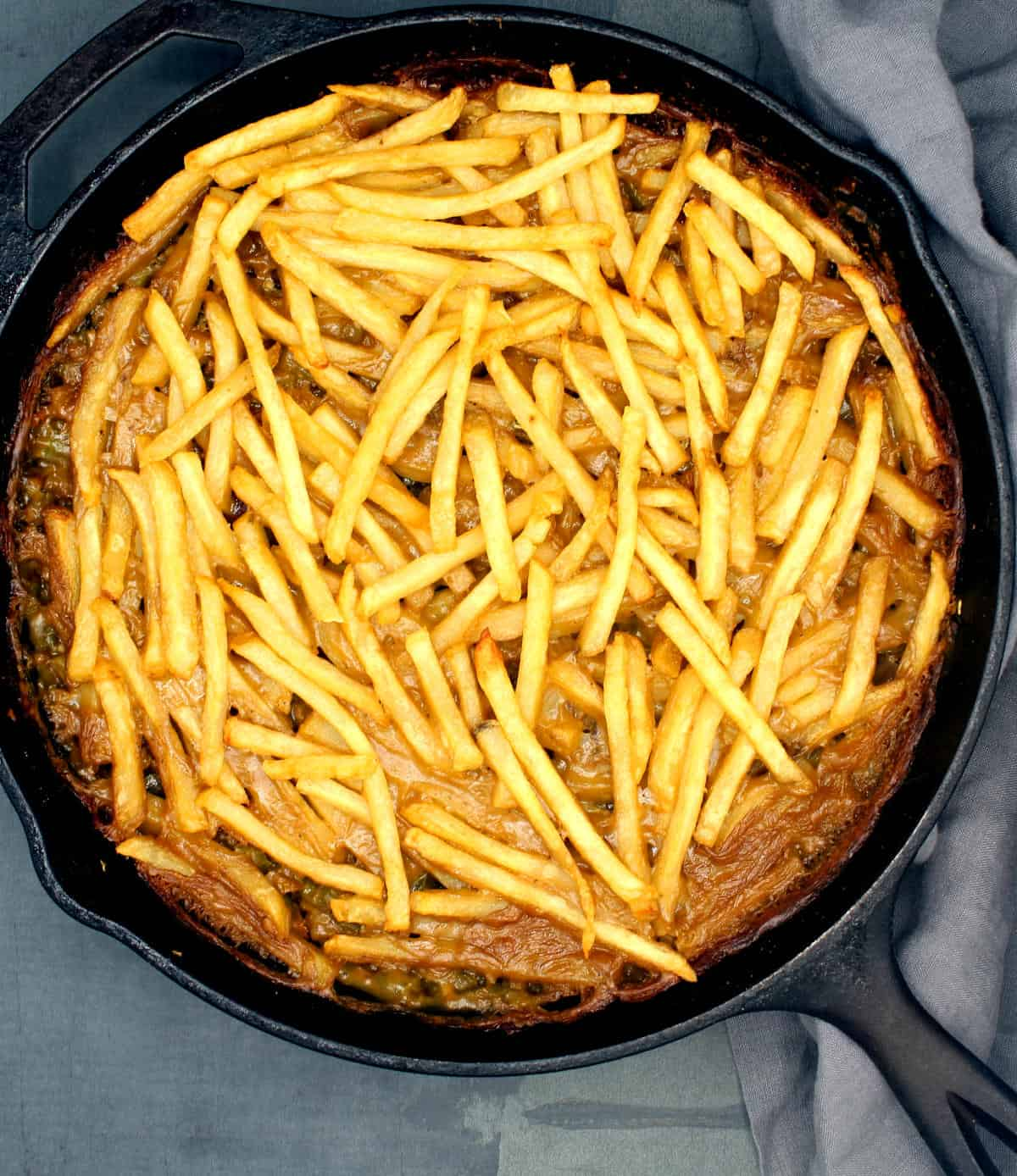 Overhead photo of a vegan French fry casserole in cast iron skillet with gray napkin.