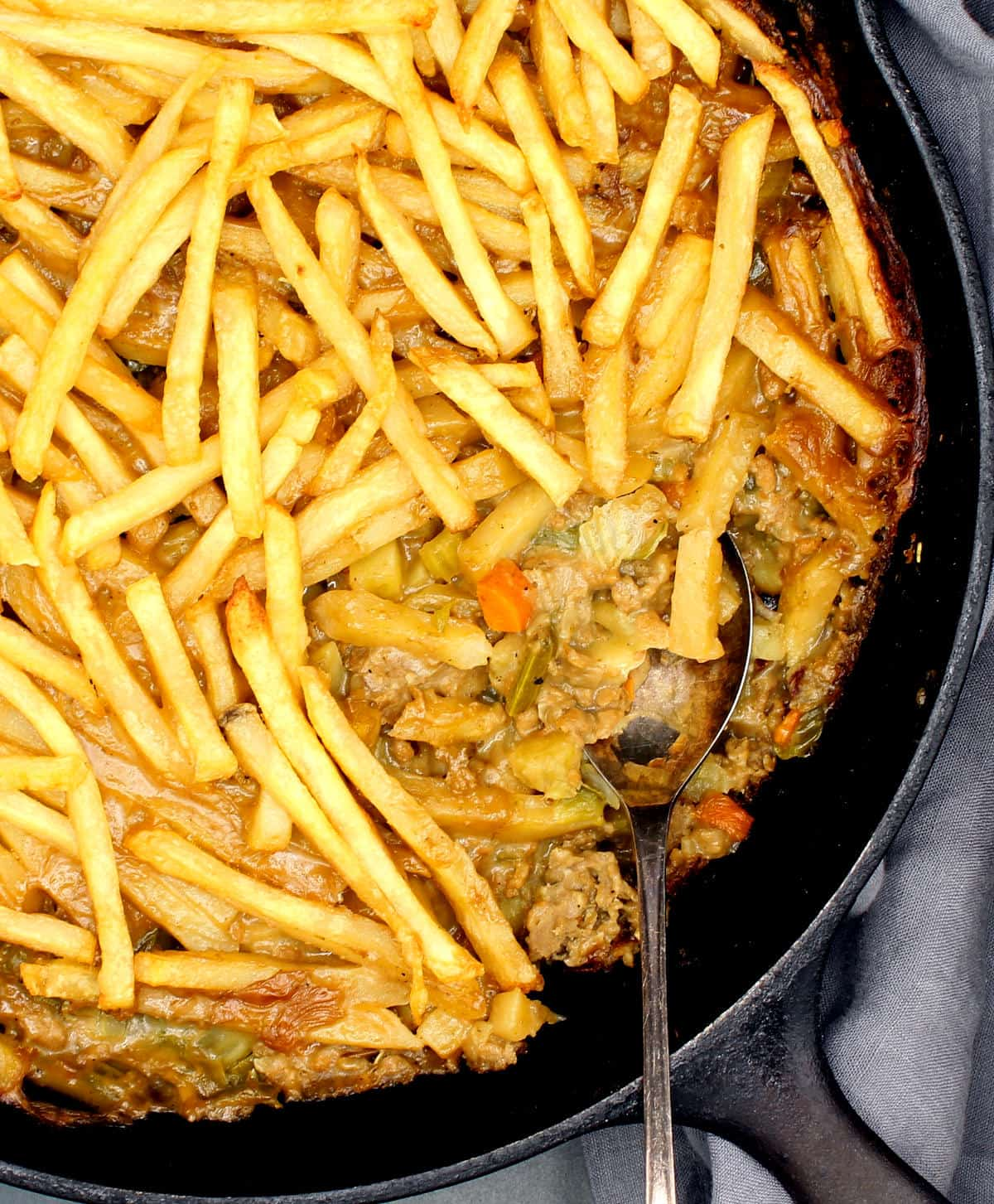Closeup photo of crispy golden French fries layered over a creamy filling of vegetables and vegan meat in a cast iron skillet.