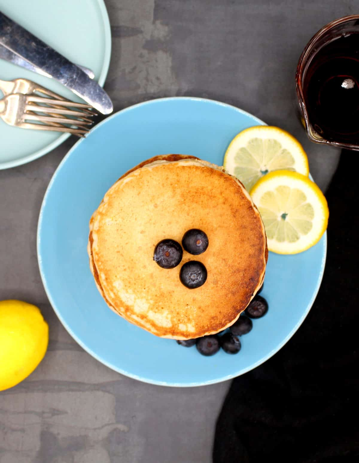 Overhead photo of vegan lemon pancake with blueberries and lemons and maple syrup.