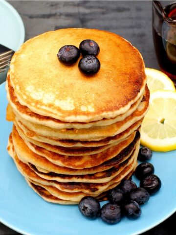 A tall stack of vegan lemon pancakes with lemon slices and blueberries on a blue plate.