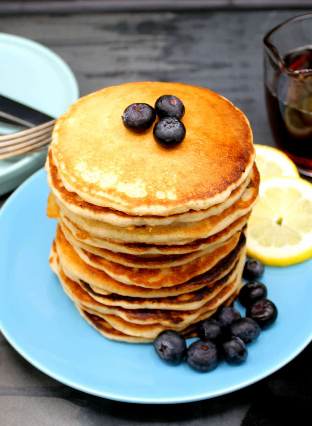 A tall stack of vegan lemon pancakes on a blue plate with blueberries and lemon slices and maple syrup on side.