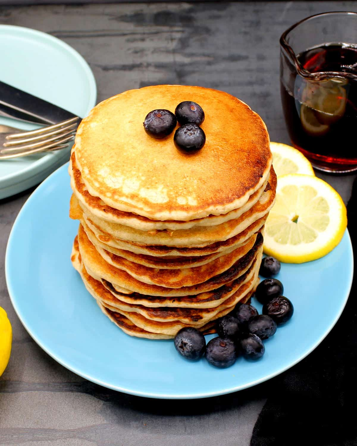 Front overhead photo of a stack of vegan lemon pancakes served on a blue plate with blueberries. On the side are lemon slices and maple syrup.