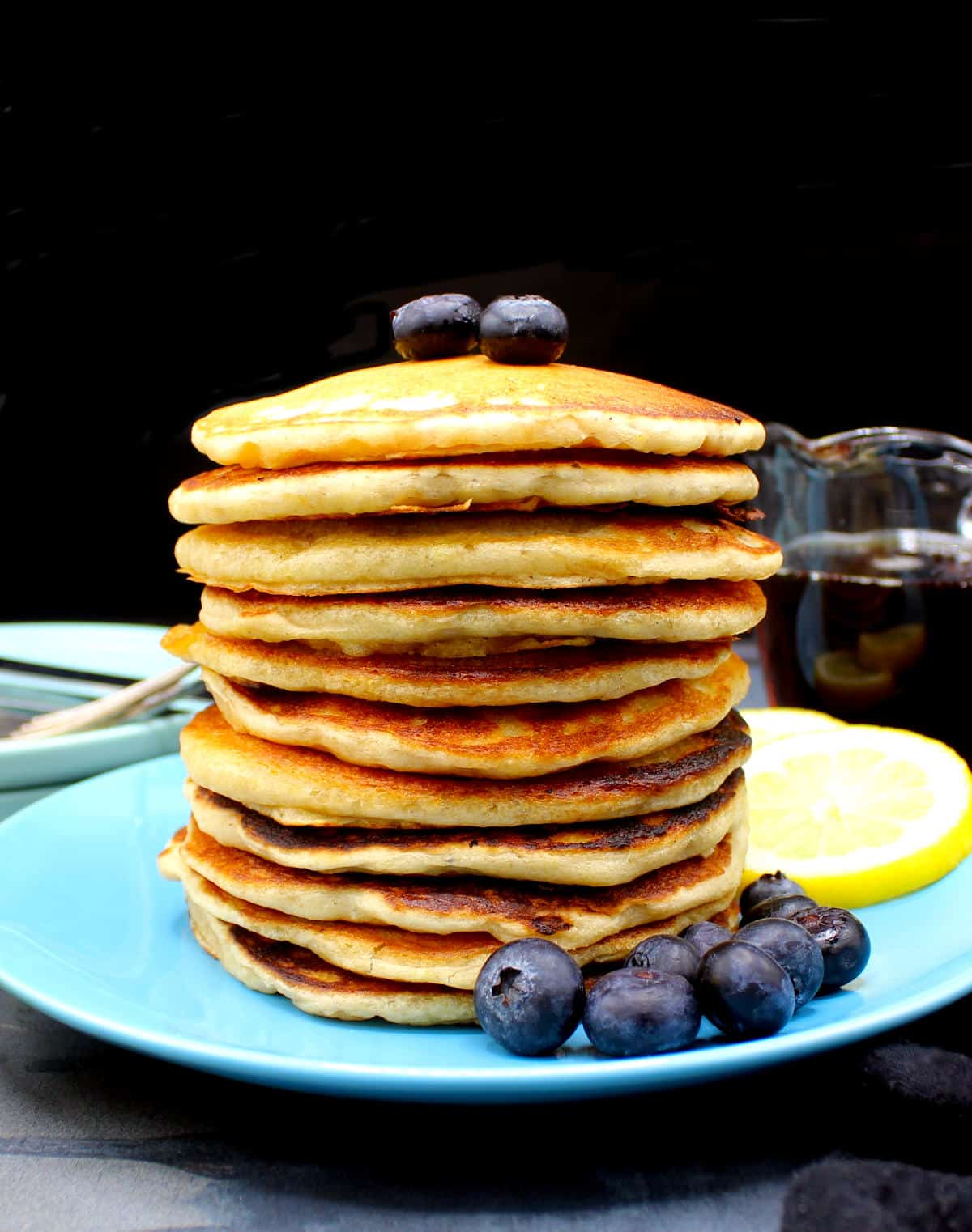 Front photo of a stack of vegan pancakes with lemon and blueberries and maple syrup.