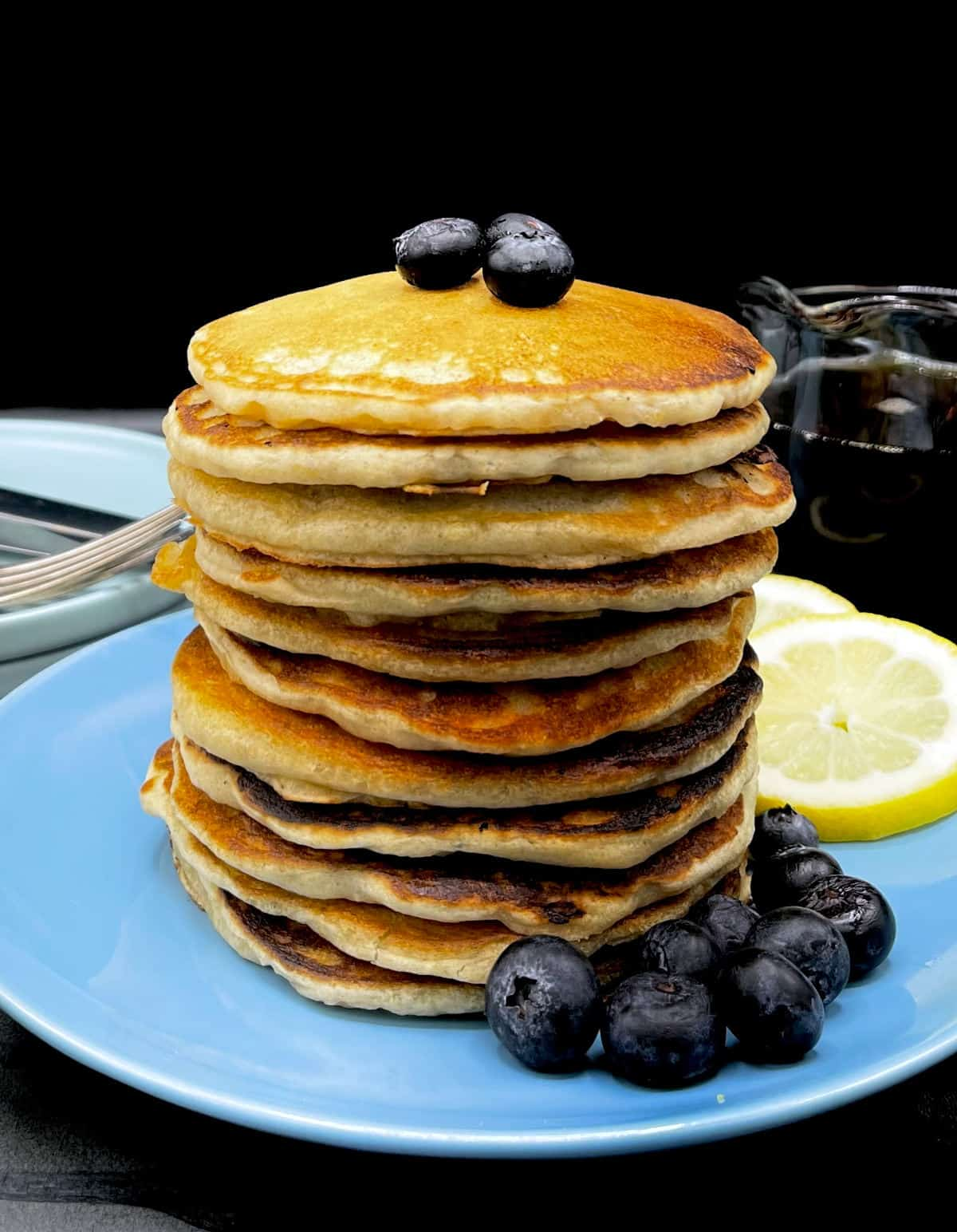 Front photo of a stack of vegan lemon pancakes with blueberries and lemon slices with maple syrup on side.