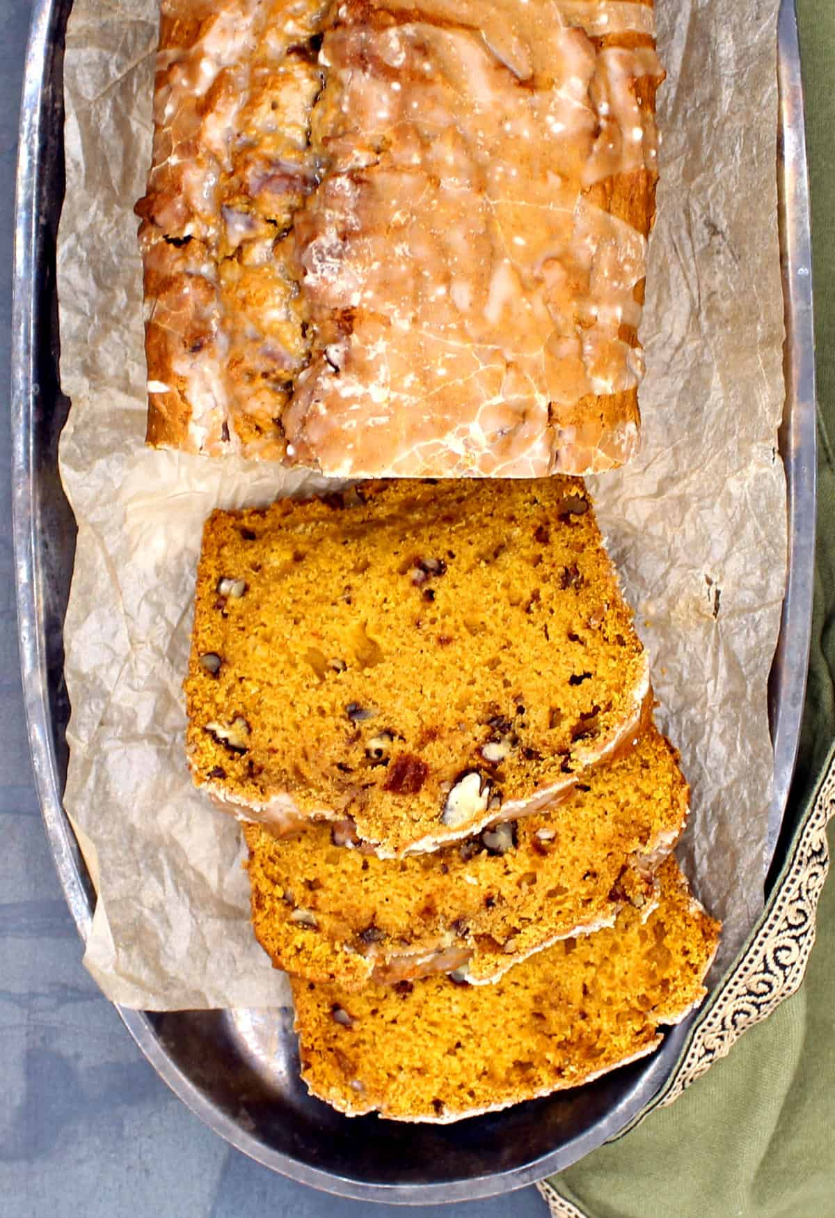 Overhead photo of a glazed vegan pumpkin bread with three moist slices with pecans on a silver tray.