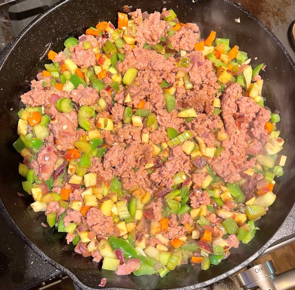 Sausage or meatless beef added to cast iron skillet.